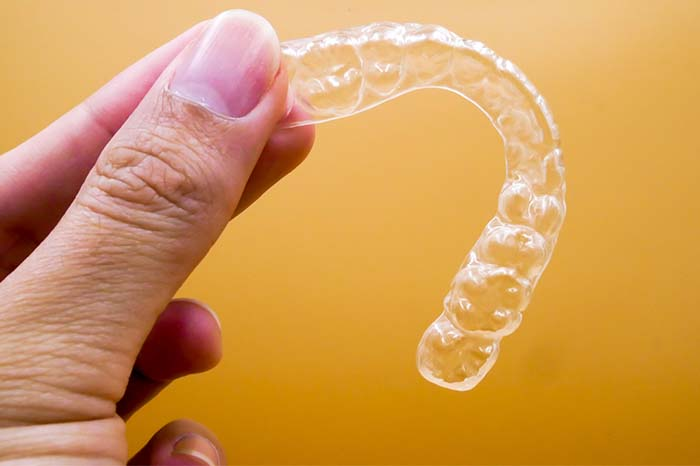 person holding clear braces in hand