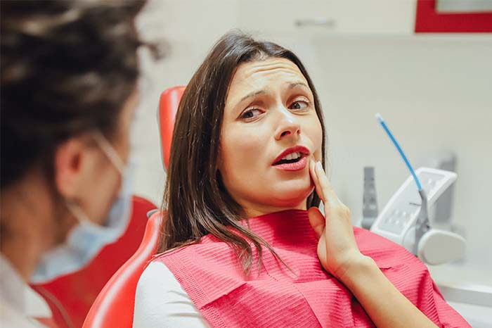Young girl with a painful tooth, a doctor in office chairs