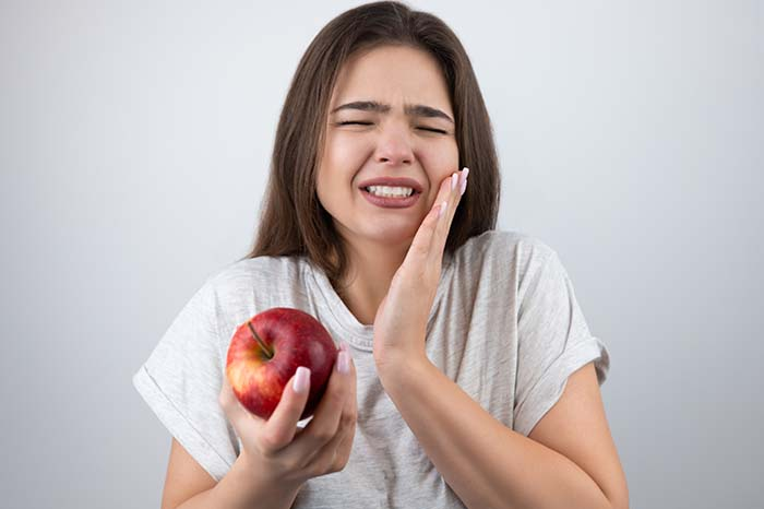 Young brunette woman suffering toothache holding red apple
