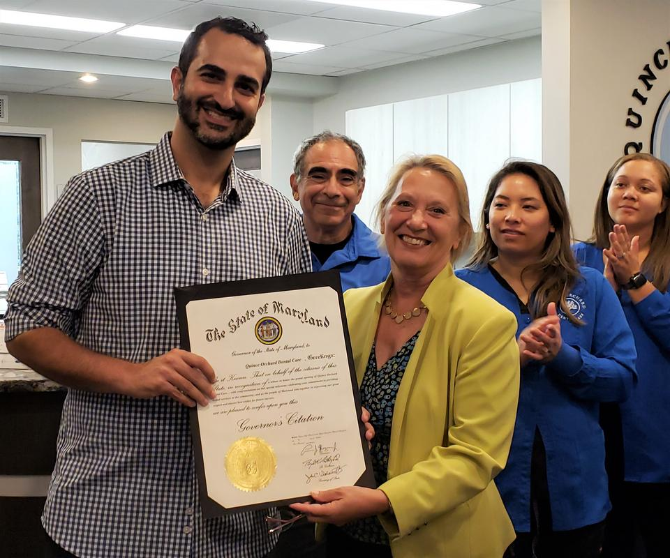 Photo of Dr. M. Mehran Rouhanian, presented the Governor's citation County from Gaithersburg-Germantown Chamber of Commerce, President Marilyn Balcombe at the dental practice's ribbon cutting ceremony.