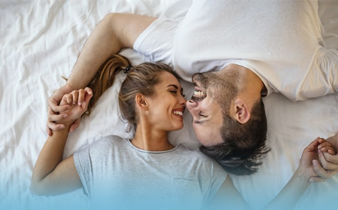 Photo of a happy couple lying on a bed