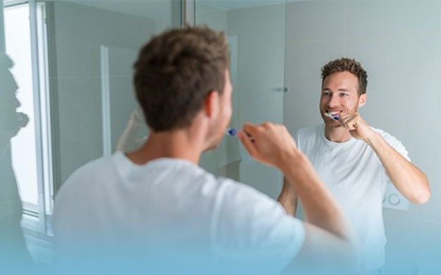 Photo of adult male brushing his teeth