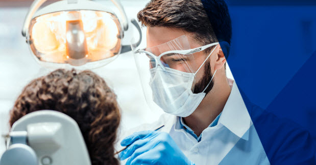 Photo of dentist in mask and face-shield