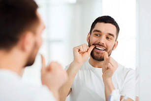 Photo of a man flossing