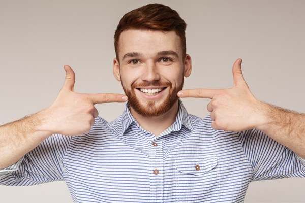 Photo of man smiling and pointing to his teeth