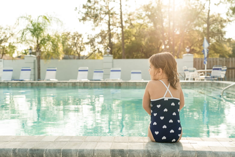 Young girl sitting at the poolside