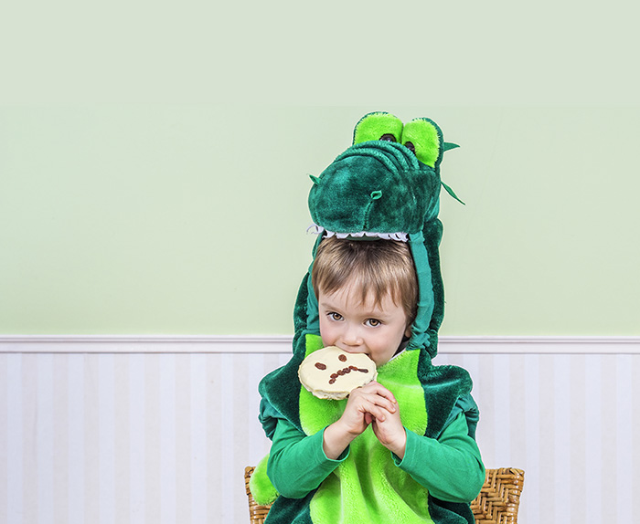 Photo of a little boy in costume eating a cookie