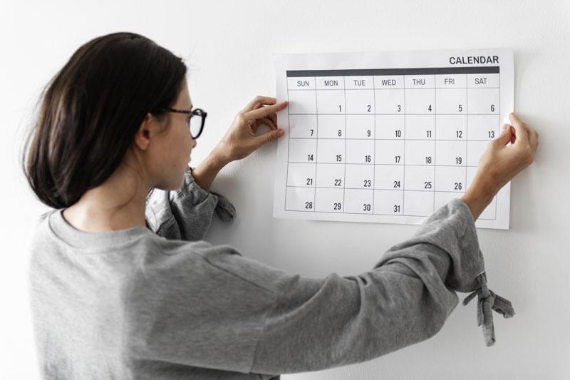 Photo of a woman hanging a calendar