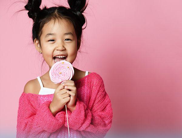 Photo of a little girl eating a lollipop